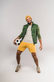 Positiver Sportler in Freizeitkleidung mit Fußball auf grauem Hintergrund