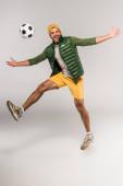 Positiver Mann springt in der Nähe von Fußball in der Luft auf grauem Hintergrund