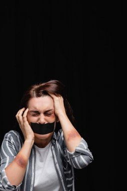 Depressed woman with bruises and adhesive tape on mouth isolated on black stock vector