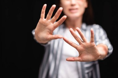 Cropped view of victim of domestic violence on blurred background showing shop gesture isolated on black