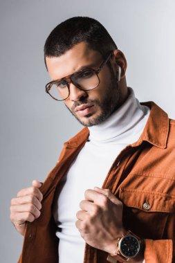 Stylish man in wireless earphone holding jacket on grey background stock vector