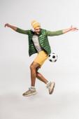 Fröhlicher Sportler mit Kopfhörern, der in Fußballnähe auf grauem Hintergrund springt
