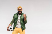 Excited sportsman in casual clothes showing yeah gesture and holding football isolated on grey