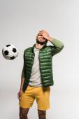 Sportember fedő arc kézzel közel futball levegő elszigetelt szürke