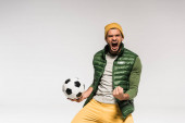 Excited sportsman with open mouth showing yes gesture and holding football isolated on grey