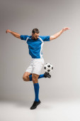 Athletic man exercising with football on grey background