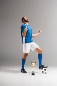 Sportler feiert Triumph neben Fußball und Meisterpokal auf grauem Hintergrund