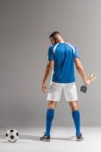 Zadní pohled na sportovce s pohárem mistrů při pohledu na fotbal na šedém pozadí