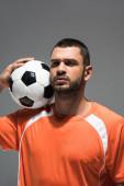 Komoly sportoló, foci nézi a kamerát, miközben elszigetelve áll a szürke