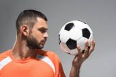 Fiatal szakállas sportoló nézi labdarúgás elszigetelt szürke