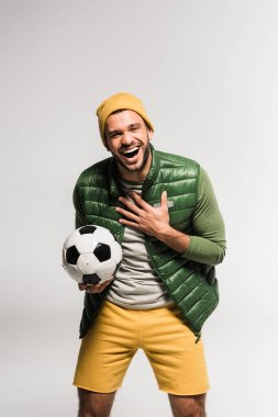 Cheerful sportsman holding football and looking at camera on grey background stock vector