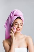 krásná žena s ručníkem na vlasy pomocí houby se zavřenýma očima izolované na šedé
