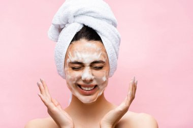 Smiling beautiful woman with towel on hair and foam on face isolated on pink stock vector