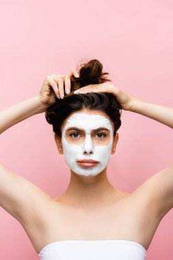 sad beautiful woman with clay mask on face isolated on pink