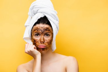 Sad beautiful woman with towel on head and coffee mask on face isolated on yellow stock vector