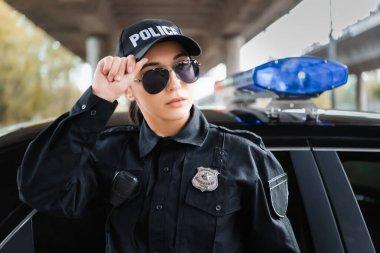 Polis arabasının yanına bakan genç bir bayan. Arka planda bulanıklık var.