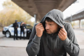 frightened hooded offender hiding with blurred police officers on background outdoors