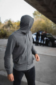 hooded thief looking away with blurred multicultural police officers on background outdoors