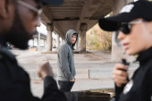 dissatisfied hooded offender looking at blurred multicultural police officers on foreground on urban street