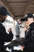 policewoman talking on radio set near african american colleague pointing with finger at blurred offender on background outdoors