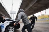 hooded offender running from multicultural police officers near patrol car on urban street