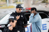 Photo policeman talking with african american victim near patrol car with blurred colleague on foreground outdoors