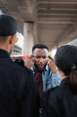 angry african american victim showing you are insane gesture while arguing with police officers on blurred foreground outdoors