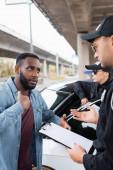 Afrikai amerikai áldozat beszél rendőr tartja írótábla homályos háttér szabadban