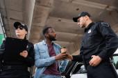 Nízký úhel pohledu policista dává kávu jít do africké americké oběti v blízkosti kolegy s podložkou a auto venku