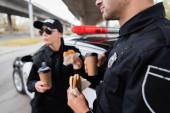 Policista držící burger a kávu jít blízko kolegy a auto na rozmazané pozadí na městské ulici