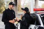 Usmívající se policista drží odnášející kávu a burger poblíž kolegy při obědě poblíž auta venku