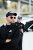 Photo Policeman in sunglasses standing with crossed arms near colleague and auto on blurred background