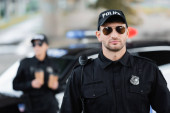 Photo Officer of police in sunglasses near colleague and car on blurred background outdoors