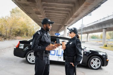 Multicultural police officers with paper cups talking near patrol car on blurred background on urban street stock vector