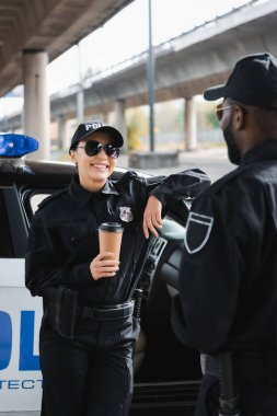 Happy policewoman with paper cup looking at african american colleague while leaning on patrol car on blurred background stock vector