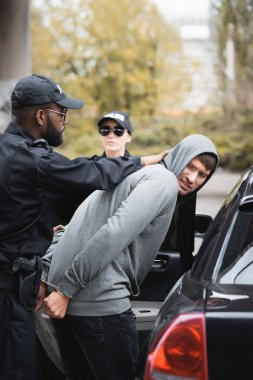 african american policeman arresting angry hooded offender near colleague and patrol car on blurred background outdoors