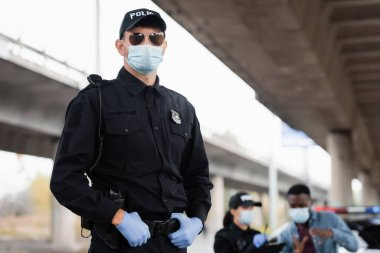 Police officer in medical mask and latex gloves standing near colleague and african american victim on blurred background outdoors stock vector