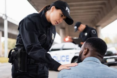 Policewoman calming african american man near colleague on blurred background on urban street stock vector