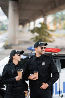 Smiling officers of police in sunglasses holding coffee to go near auto on blurred background on urban street stock vector