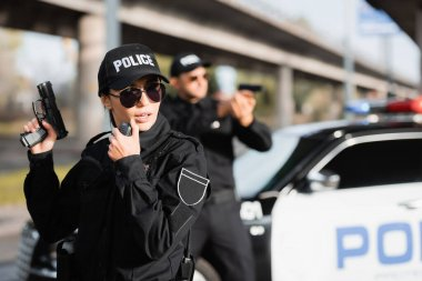 Policewoman in sunglasses holding gun and using walkie talkie near colleague and car on blurred background stock vector
