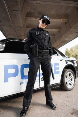 Policewoman in uniform and sunglasses standing near car on urban street stock vector