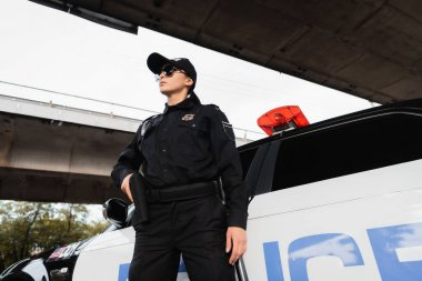 Policewoman in sunglasses holding gun in holster near car on urban street stock vector