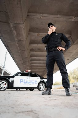 Low angle view of policeman in sunglasses standing with hand on hip near car on blurred background on urban street stock vector