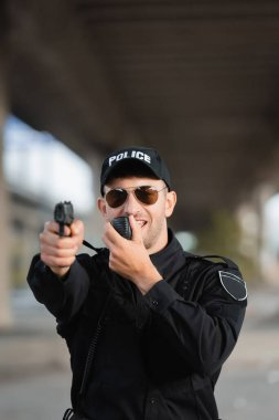 Police officer in sunglasses using walkie talkie and holding gun on blurred foreground outdoors stock vector