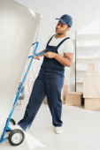 strong indian workman holding hand truck while moving fridge in apartment