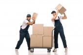 plná délka šokovaných multikulturních stěhováků v uniformách s kartonovými krabicemi poblíž ručního vozu s balíčky na bílém