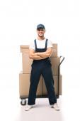 plná délka veselého pohybu v uniformě a čepici stojící se zkříženýma rukama v blízkosti ručního vozu s kartonovými krabicemi na bílém