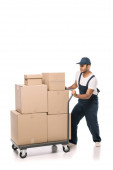 full length of indian mover in overalls pulling heavy hand truck with carton boxes on white