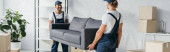 Photo smiling multiethnic movers in uniform carrying couch in apartment, banner