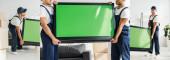 koláž multikulturních stěhováků v uniformě nesoucích plazmovou televizi se zelenou obrazovkou v bytě